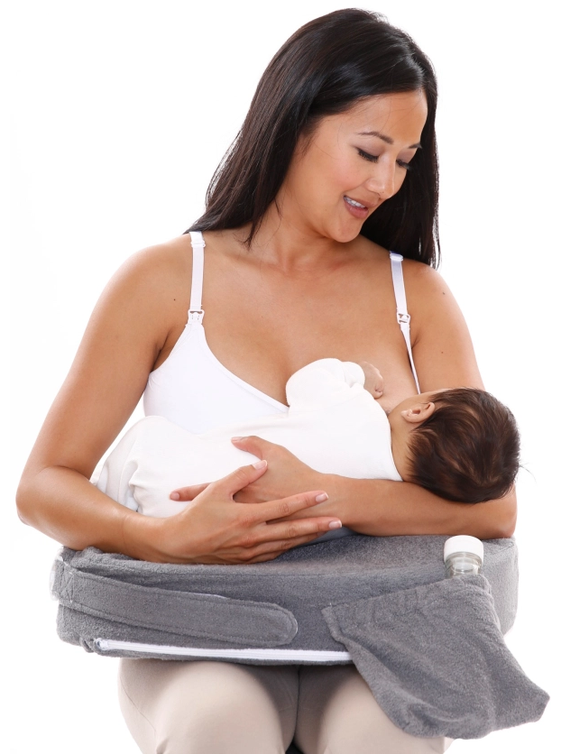 image of woman smiling down while breastfeeding with my brest friend pillow
