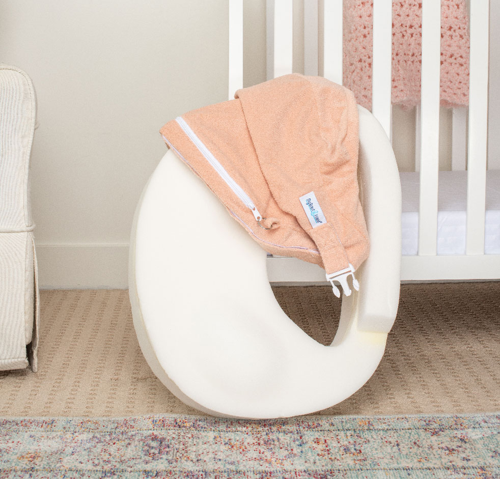 My Brest Friend pillow draped with cover in front of crib